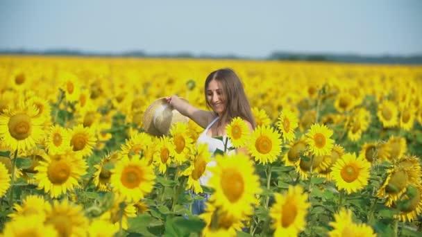 lány egy kalapban a háttérben a napraforgó virágok