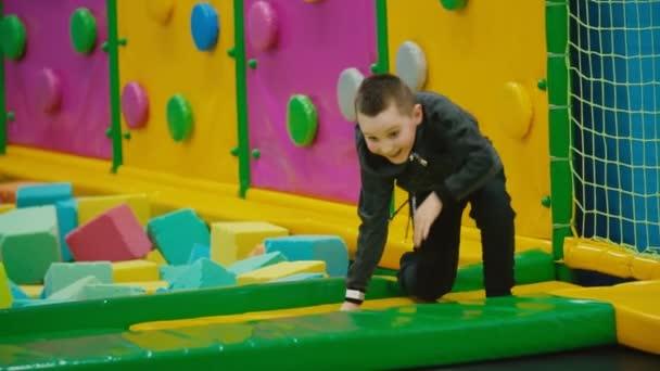 chlapec šplhá po trampolce a padá