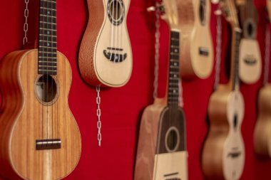 Close up view of a group of small classic four string guitars.