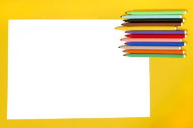 set of felt pens with white paper on a yellow background.