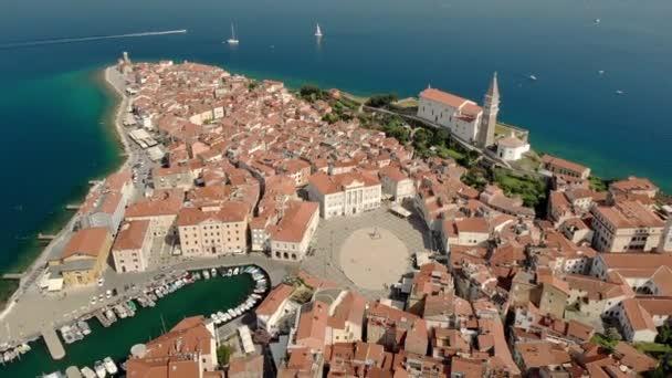 Krásné vzdušné video města Piran s Tartini hlavní náměstí, starobylé domy s červenými střechami a Jaderského moře ve Slovinsku