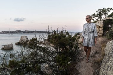 Beautiful woman in luxury summer dress enjoying peaceful seascape of Porto Rafael bay at Mediterranean sea of Costa Smeralda, Sardinia, Italy at dusk
