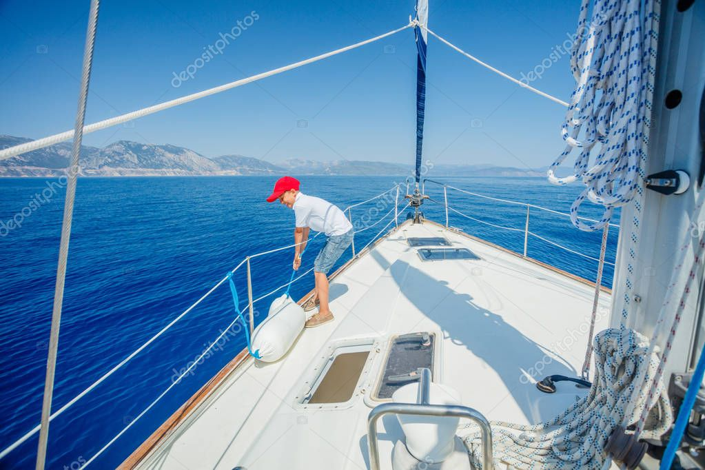 Little boy on board of sailing yacht on summer cruise.