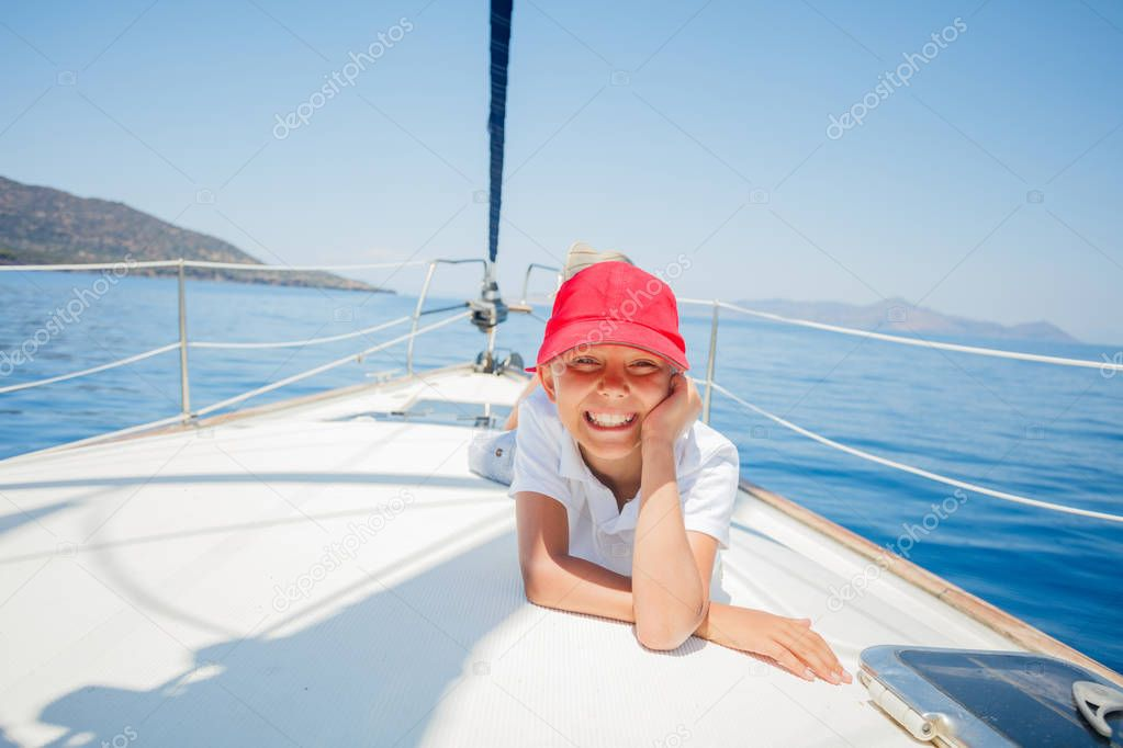 Little boy having fun on yacht on summer cruise. Travel adventure, yachting with child on family vacation.