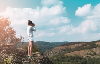 woman photographer takes a picture of a mountain landscape on the camera