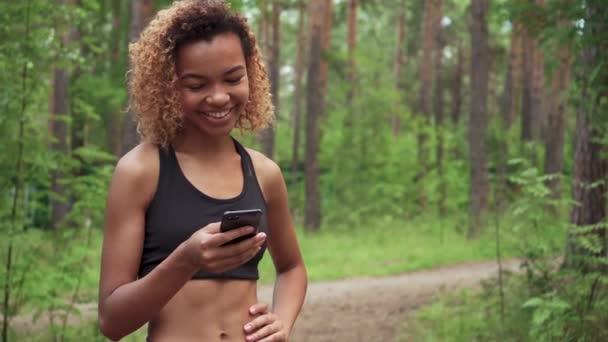 junge schöne afrikanisch-amerikanische Frau mit lockigem Haar plaudert vor dem Joggen mit ihrem Handy