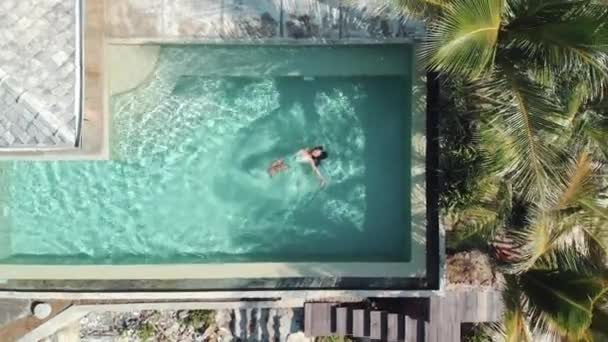 A young glamorous woman in a bikini in a pool in a luxury villa. aerial view