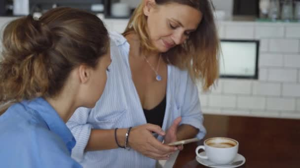 Women having date in cafe. One Sharing something Exciting on her Mobile Phone