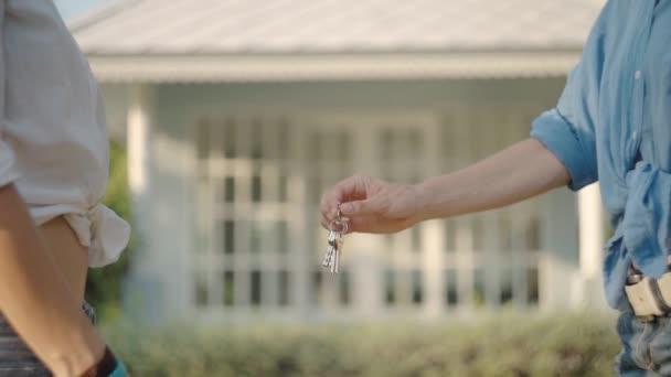 Agente immobiliare che dà le chiavi di nuovi proprietari di proprietà. ora legale