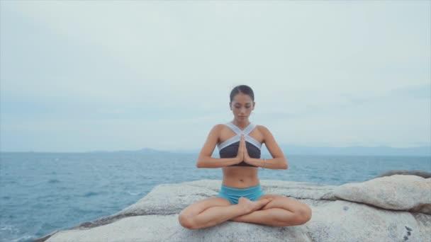 Žena, která sedí na skalách před oceánem a medituje