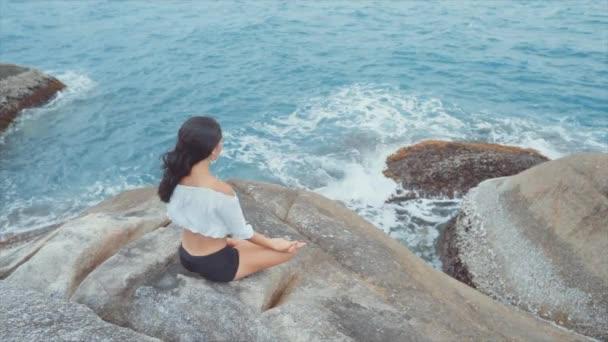 Frau sitzt am Meer und meditiert im Hochwinkel