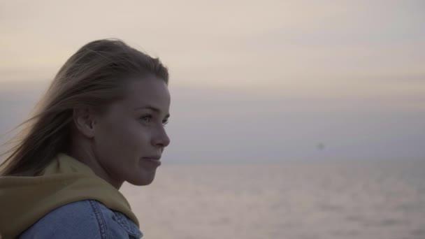 Konterfei einer jungen Frau bei Sonnenuntergang über dem Meer