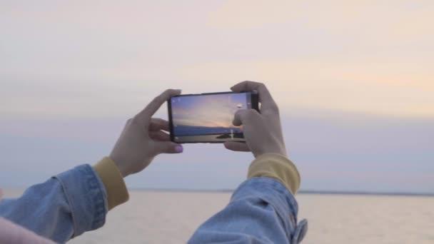 Weibliche Hände mit Handy machen Sonnenuntergang am Meer Foto