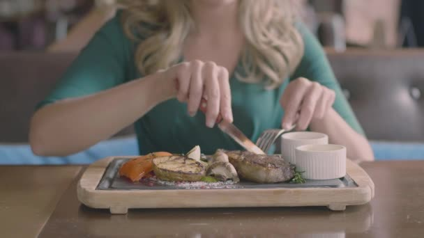 Frauenhände schneiden im Restaurant ein Steak
