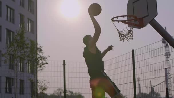 Junger Mann schießt Ball in Basketballkorb