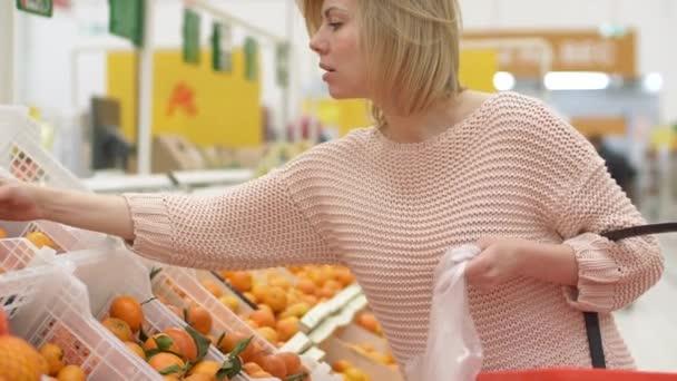 Atraktivní ležérní žena výběr oranžové ovoce zelenina supermarket tržiště