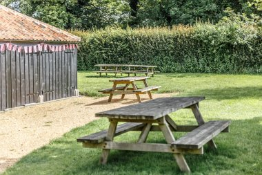 View of several wooden benches for picnic in a recreation area, UK
