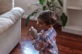 A pályázat gyermek játszik az ő nyuszi baba a nappaliban a h