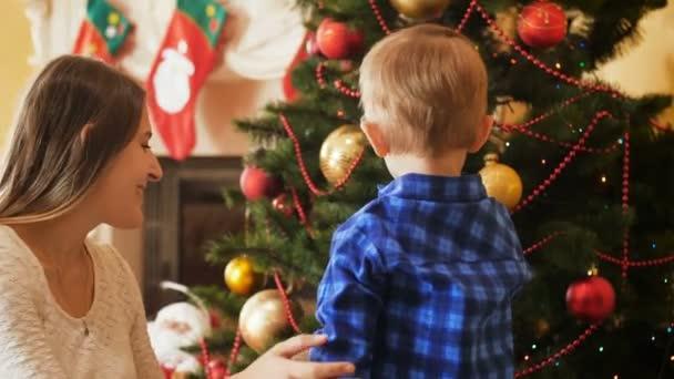 4 k Video Kleinkindes kleiner Junge schmücken Weihnachtsbaum mit Kugeln