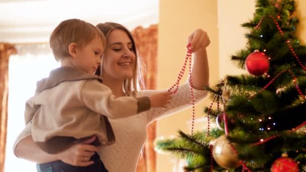 4 k Aufnahmen von niedlichen Kleinkind Junge mit Mutter dekorieren Weihnachtsbaum mit bunten Girlanden und Perlen