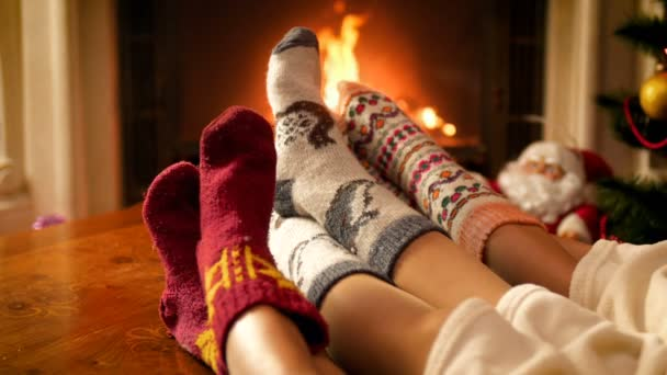 4k video of family in warm woolen socks sitting by the fireplace on Christmas eve