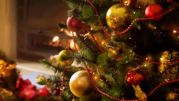 Nahaufnahme 4k Filmmaterial von schönen leuchtenden bunten Lichtern am Weihnachtsbaum gegen den brennenden Kamin im Wohnzimmer
