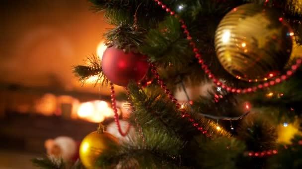 Closeup 4k záběry z červených cetka zavěšení na vánoční stromeček proti hořící krb