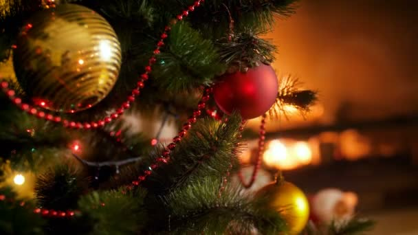 Closeup 4k video of beautiful decorated Christmas tree with red and golden baubles against burning fireplace. Perfect background for winter celebrations and holidays