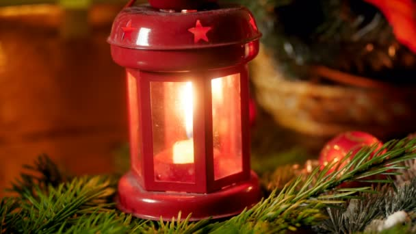 Closeup 4k footage of red lantern with burning candle on Christmas tree branch. Perfect background for winter celebrations and holidays