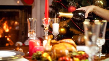 Closeup image of hand filling glasses with champagne on Christmas dining table