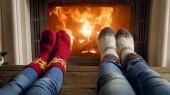Detailní fotografie páru na sobě džíny a pletené vlněné ponožky, ležící u krbu