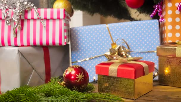 Closeup 4k footage of baubles, glowing garlands and gift boxes under Christmas tree at living room