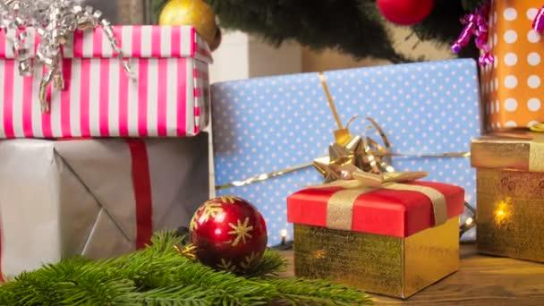 Closeup 4k záběry z kouliček, zářící girlandy a dárkové krabice pod vánoční stromeček v obýváku