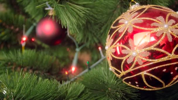 Nahaufnahme 4k Filmmaterial von leuchtend roter Christbaumkugel und Lichterkranz auf Weihnachtsbaumzweigen