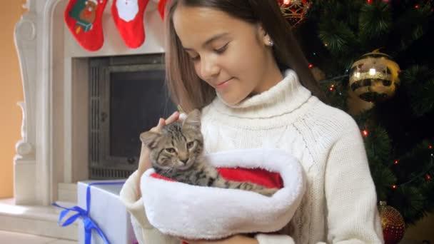 Portrait of beautiful teenage girl caressing cute kitten sitting in Santa cap next to Christmas tree