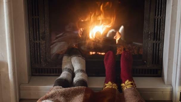 4 k záběry ze dvou lidí, oteplování nohama do vlněné pletené ponožky v hořící krb
