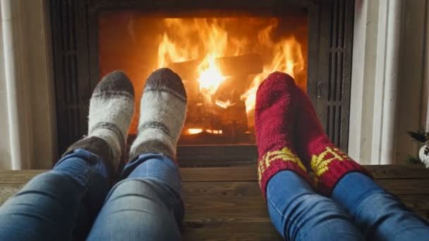 Closeup toned footage of romantic couple in woolen socks lying by the burning fireplace