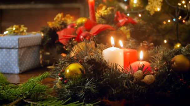 Nahaufnahme 4k Filmmaterial von drei brennenden Kerzen auf dem Weihnachtskranz