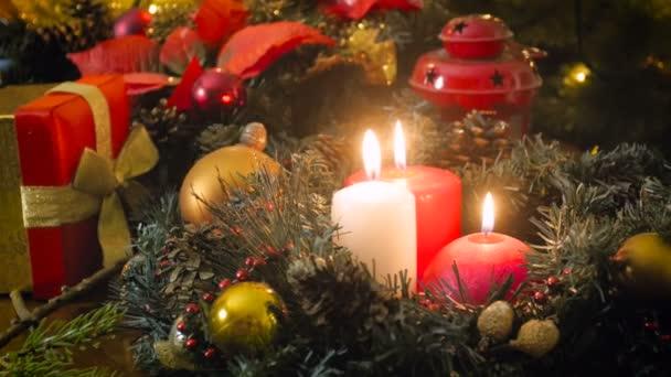 Nahaufnahme 4k-Video von Kamerafahrten entlang brennender Kerzen im traditionellen Weihnachtskranz
