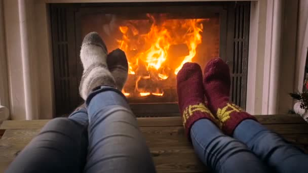 Closeup slow motion footage of family enjoying lying by the burning fireplace at house