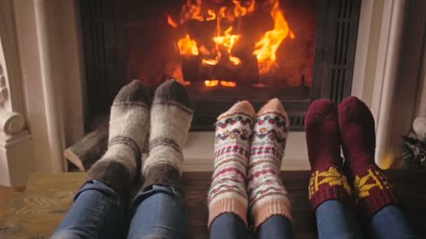 Zpomalené video rodiny s dítětem v pletené vlněné ponožky, odpočinku u krbu