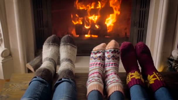 Slow motion video of young family wearing knitted socks warming by the fireplace at living room