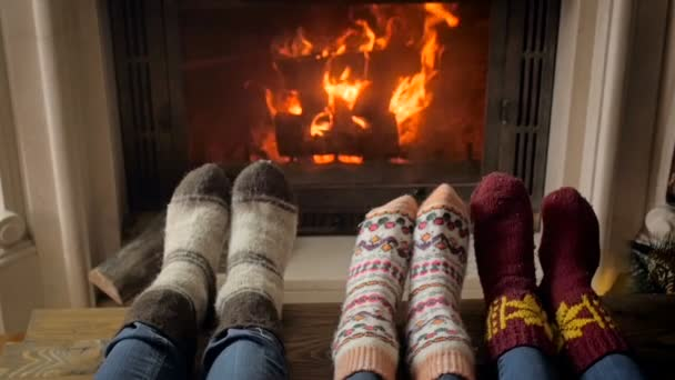Slow motion video of family in warm socks lying in living room next to burning fireplace