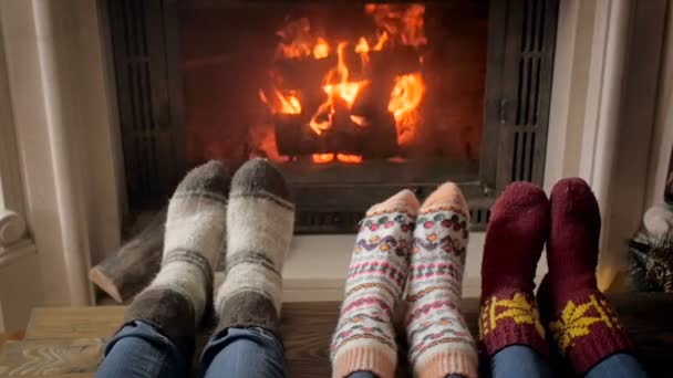 Slow motion footage of young family in socks lying next to burning firepalce at night