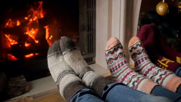Slow motion footage of family in woolen knitted socks lying at burning fireplace on Christmas eve