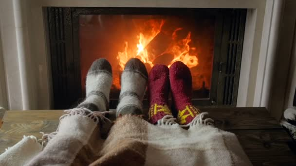 Slow motion video of roamntic couple lying under blanket and warming feet by burning fireplace at night