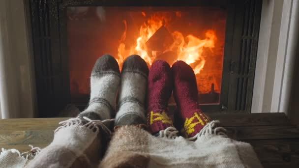 Tónovaný zpomalené video páru nosí pletené vlněné ponožky relaxační na hořící krb