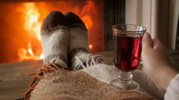 Slow motion footage of woman wearing warm woolen socks drinking tea by the fireplace