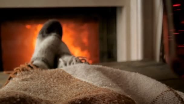 Closeup slow motion video of young woman holding cup of hot tea and resting by the burning fireplace