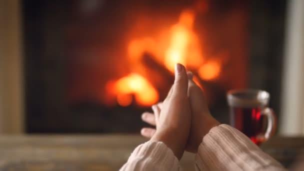 Nahaufnahme-Video einer jungen Frau in weißem Wollpullover, die kalte Hände am brennenden Kamin im Wohnzimmer wärmt